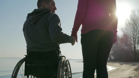handicapped love, invalid person on wheel chair with girl, happy cripple in wheelchair