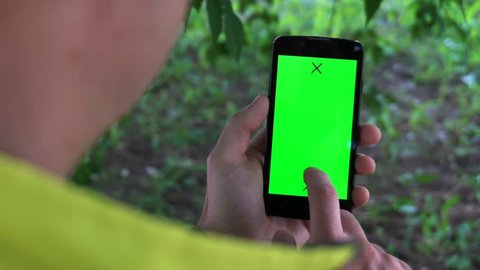 Closeup of male hands holding smartphone with green screen-prekeyed effects.nature in the background.
