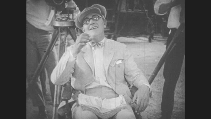 1920s: man sits next to movie camera. lion walks past window of bar set as men run away and man. A drinks at table. woman holds rope  and walks big cat. lion roars.