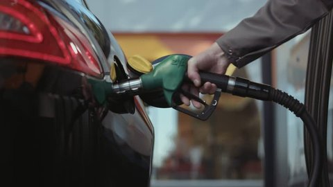 Multiple shots of a gas pump inserted in car tank. Slow motion.
