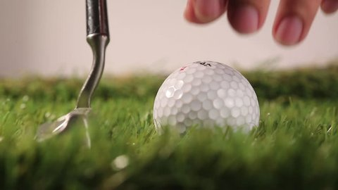 Man set a golf ball on green close up golf ball putting hit. And white background.