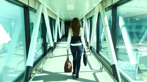 Woman walk away from airliner by glass walled passenger bridge, POV camera follow behind. Business lady arrived to destination, come to terminal building of modern international airport