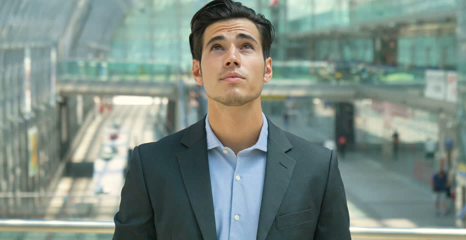 Portrait of a young handsome businessman in suit, at the station, looking up, smiling, in the background of a construction. Concept: new business, business relationships, career growth, success. | Shutterstock HD Video #27992590