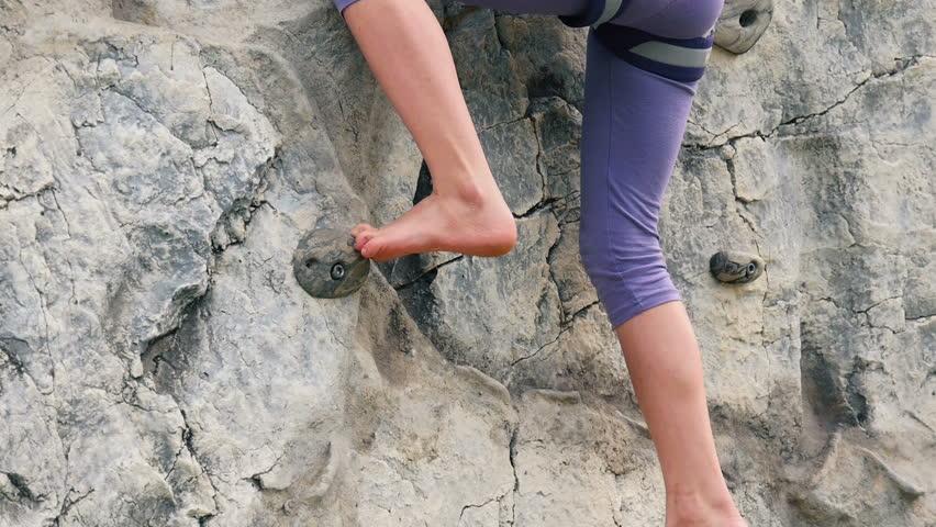 Child On An outdoor Climbing Wall. Climbing bare feet. Sloe-motion HD
