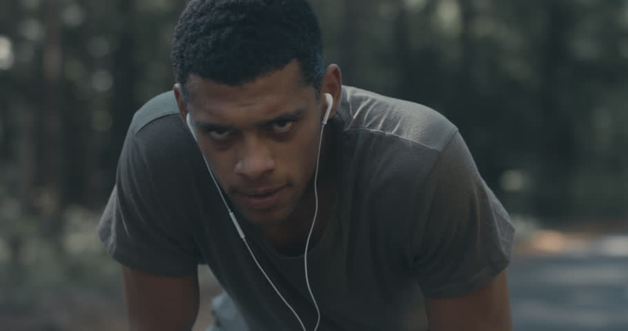 Young concentrated African American sweating while catching breath after sprinting on the forest road, looking into camera. 4K UHD