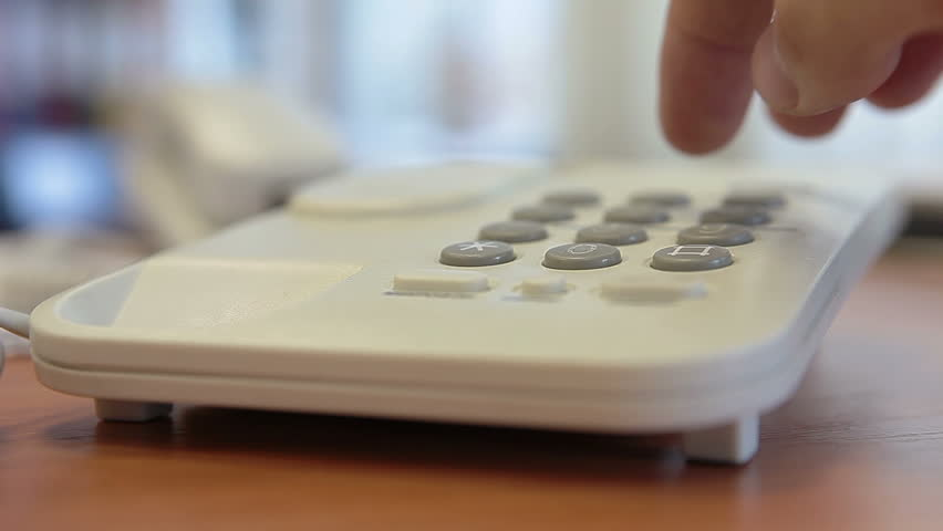 Dialing telephone number on desk phone by finger. Close up view