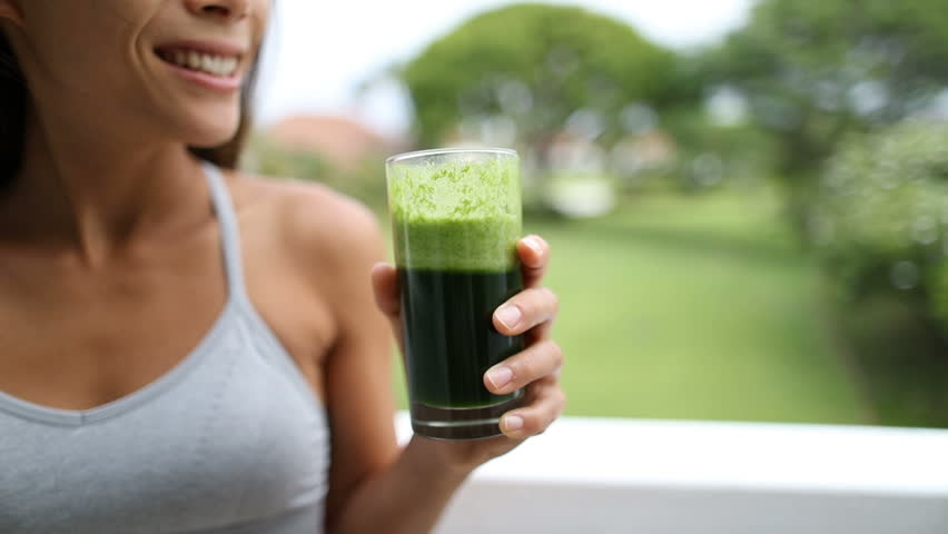 Happy young woman drinking fresh green juice enjoying detox cleanse. Fit female is enjoying healthy drink at park.