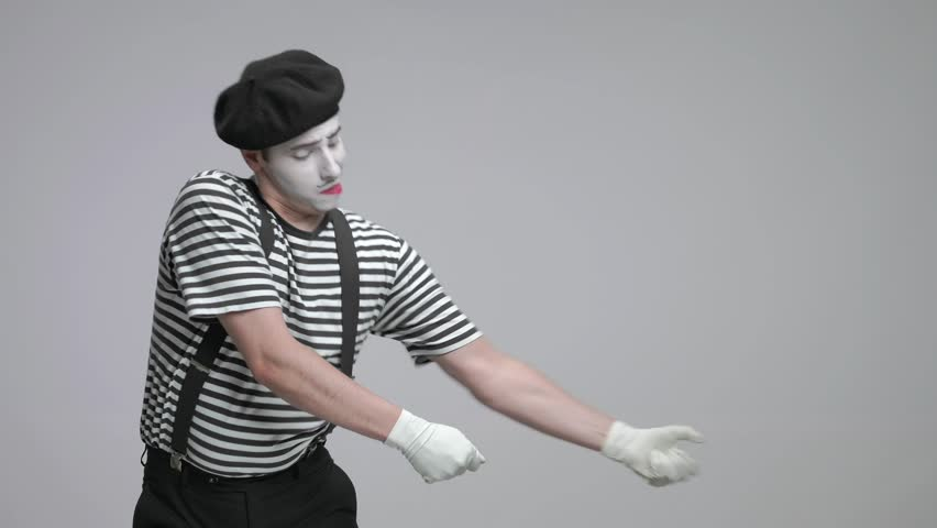 Mime pulling an imaginary rope isolated on gray background