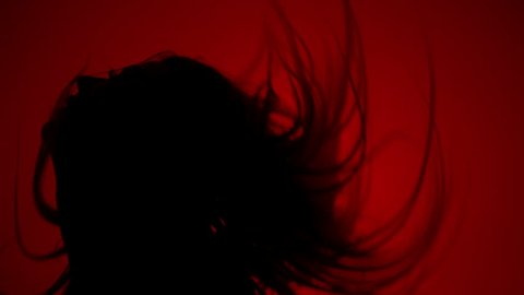 Silhouette of woman shaking hair on red background. Sexy girl silhouette in dark. Sexy woman silhouette in sexual pose in dark. Erotica concept