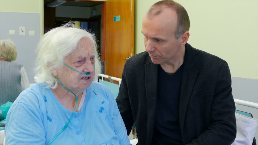 Old, Ill woman and her family member are talking in hospital room | Shutterstock HD Video #28040650