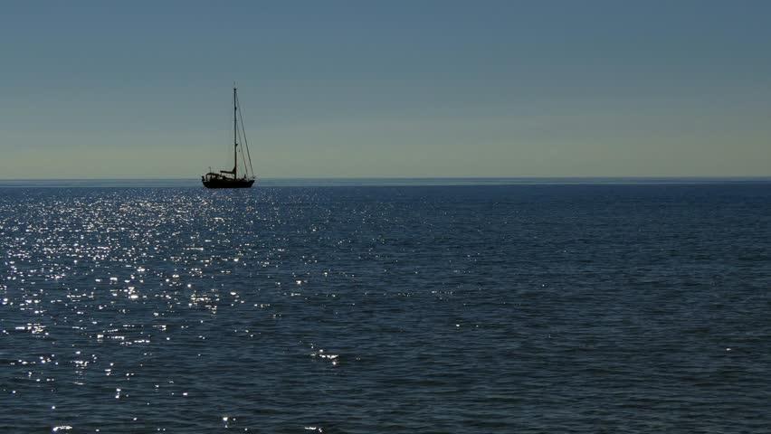 Sailing boat floating on water in Italy. Italian coast in Sardinia on Mediterranean Sea. Early morning in Sardegna, Italia