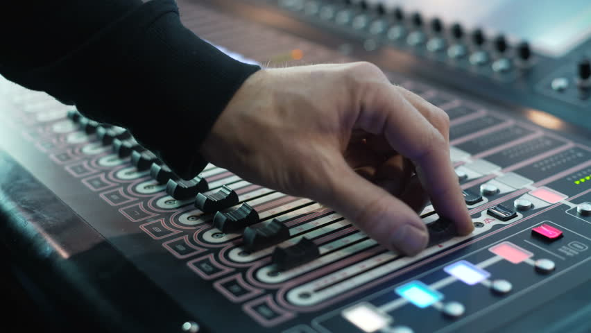 Man working on professional digital audio channel mixer in studio. Electronics for amplifier and balance of sound in show. Soundboard knobs. sound engineer presses the keys, moves the buttons. Closeup