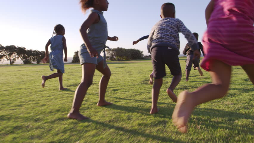 Elementary school kids chasing football in a field #28048990