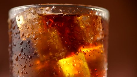 Cola with ice cubes background. Cola drink with Ice and bubbles and water drops on glass. Soda closeup. Food background. Rotation Fizzy drink. 4K UHD video footage. Ultra high definition 3840X2160