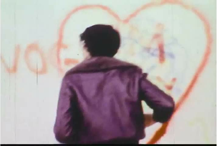 1970s: A boy is rejected by a couple, defaces a wall, and is threated by an owner of a building in the 1970s.   Shutterstock HD Video #28062130