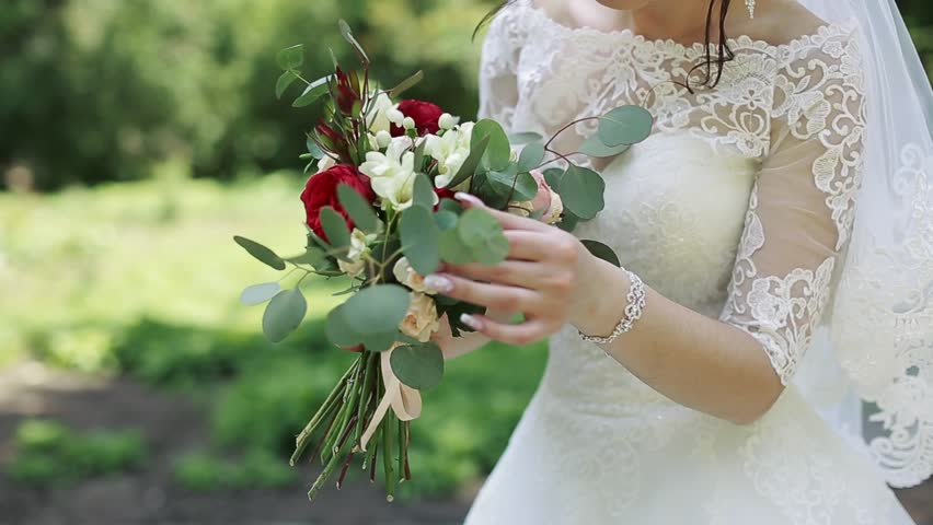 Beautiful bouquet of different colors in the hands of the bride in a white dress #28103080