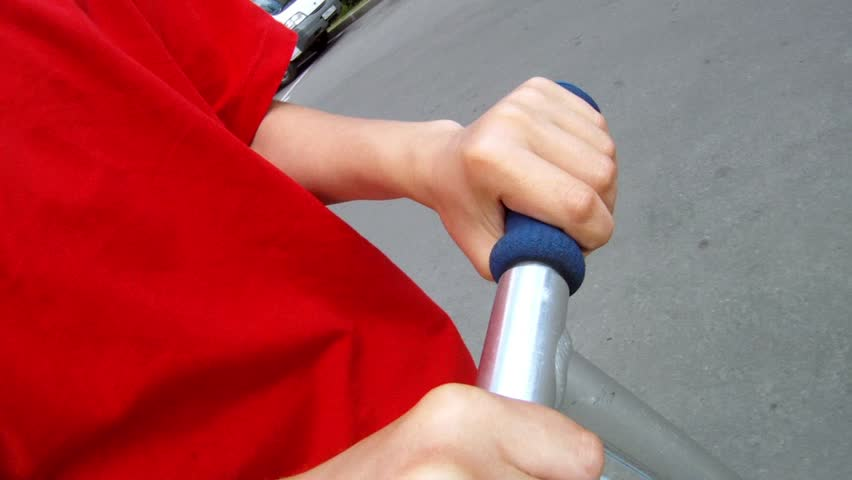 Boy in red T-shirt strong keeps in hands a scooter helm