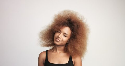 beuayt black woman with a huge afro hair having fun smiling and dancing in studio