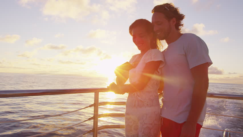 Couple using smart phone screen on sunset cruise ship sailing in ocean on vacation. Woman and man looking at smartphone app having fun on travel.