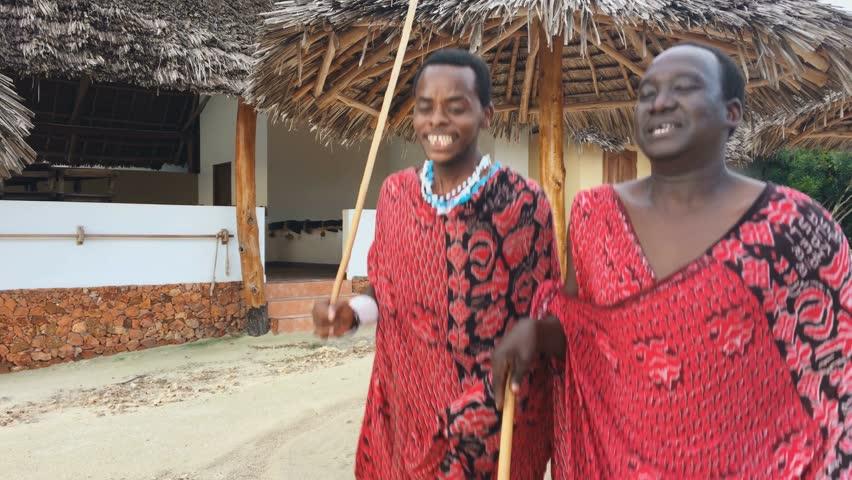 Two Masai people dances their national African dance on the Indian Ocean beach at sunset and bids farewell to the sun. Tanzania. Zanzibar. 4K.
