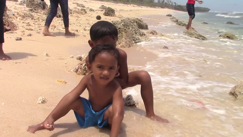 SULANGAN, PHILIPPINES - CIRCA MARCH 2017:  Filipino kids play on a beach on the ocean near the village of Sulangan, Eastern Samar, Philippines.