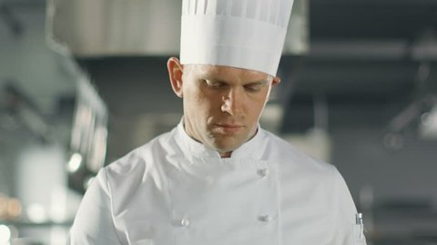 Famous Chef Concentrated on Preparing Fish Dish on a Pan. He Works in a Modern Kitchen. Shot on RED EPIC-W 8K Helium Cinema Camera.