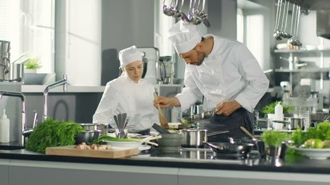 Famous Chef and His Female Apprentice Prepare Special Dish in a Modern Five Star Restaurant's Kitchen.   Shot on RED EPIC-W 8K Helium Cinema Camera.