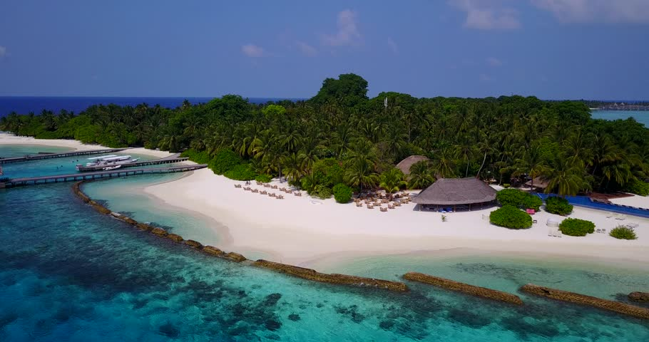 Aerial flying drone view of Maldives white sandy beach on sunny tropical paradise island with aqua blue sky sea water ocean 4k   Shutterstock HD Video #28253281