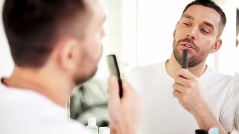 beauty, grooming and people concept - smiling young man with comb looking to mirror and singing at home bathroom