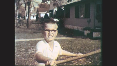 1960s: UNITED STATES: window smashes. Boys fight with wooden swords in garden.
