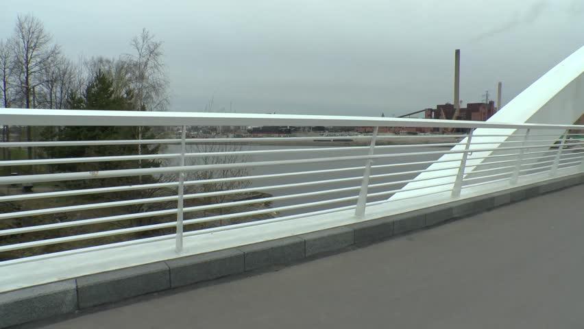HELSINKI, FINLAND - MAY 17, 2017: Unidentified man on bycicle on new bridge between Kalasatama and Mustikkamaa islands, Helsinki, Finland | Shutterstock HD Video #28288390