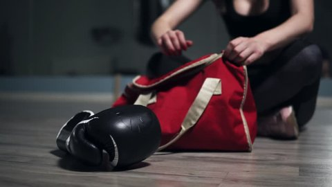 Unrecognizable woman sitting on the floor and taking from her bag gloves for boxing, preparing for training. Shot in 4k