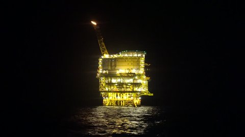 Night scenery of offshore oil rig drilling platform off the Sarawak Operation, Malaysia, South China Sea.