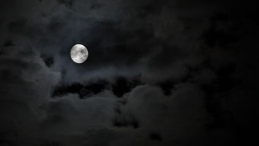Full moon behind clouds at night