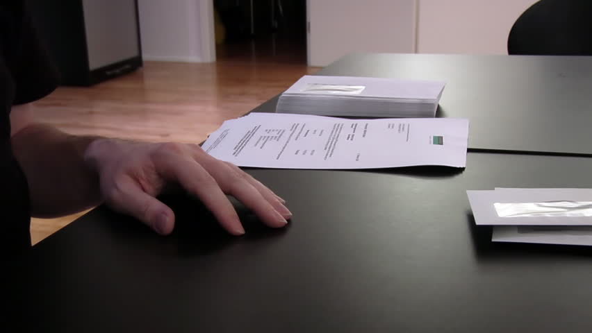 A man folding a stack of invoice letters and inserting them into envelops. Speed up at about 6:1.