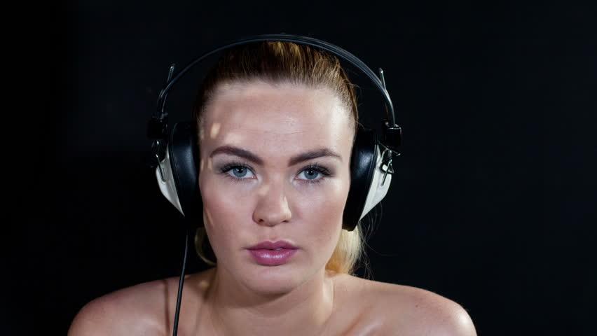 stop motion shot of a sexy gogo dancer shot in a studio dancing and posing wearing changing retro headphones