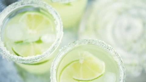Key lime margarita garnished with fresh lime and salt in mason jar on metal tray.