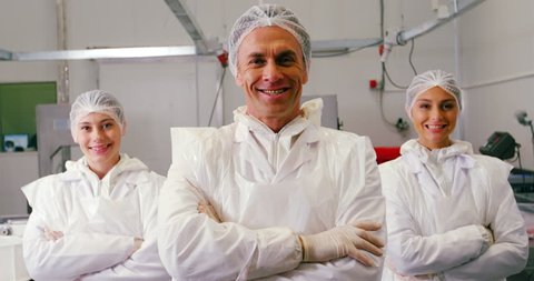 Team of smiling butcher standing with arms crossed in meat factory