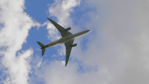 Commercial passenger airplane flying overhead on sunny day. UltraHD stock footage.