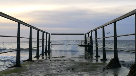 Sea waves crashing against pier in slow motion