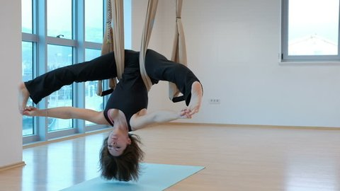 Young woman hanging upside down in hammock for yoga indoors. She slowly swings body with her legs wide apart and holds them with her fingers then she fully straightens and leans her hands on floor