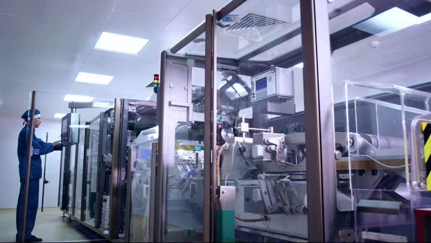 Pharmaceutical Industry Worker Operating Pharmacy Equipment Packaging Machine At Factory Manufacturing