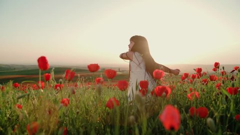 ittle Asian girl in white dress having fun in a field of red poppies in Sunny day, slow motion
