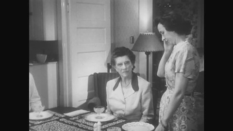 1950s: Two women and man talk in dining room. Older woman and man sit at table. Younger woman stands. Boy enters room, sits at table, picks up spoon and begins to scoop. Boy puts spoon back on table.