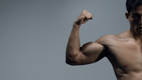 Male fitness model flexes his bicep and stretches out his arm. Close up.