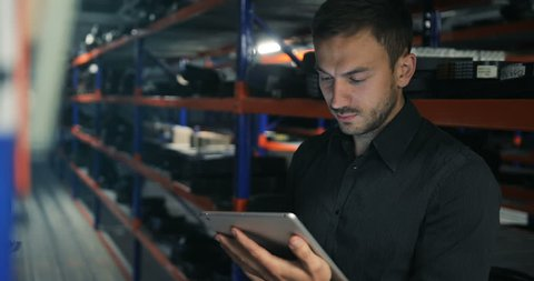 Serious strict warehouse manager using tablet pc in a large warehouse perspective