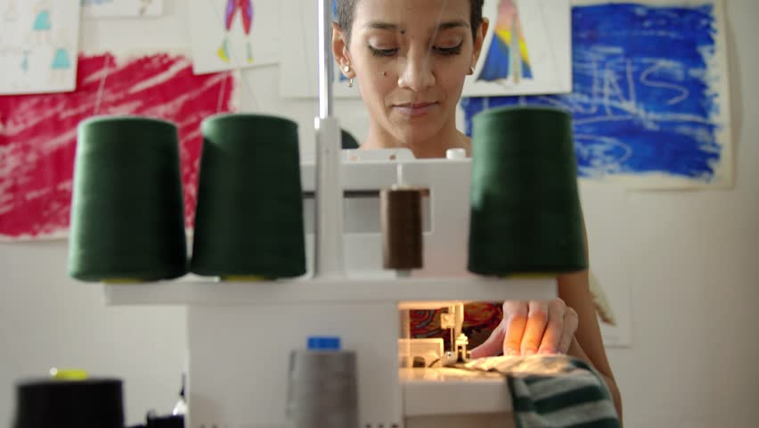 Young hispanic woman working as fashion designer with sewing machine in studio. Sequence