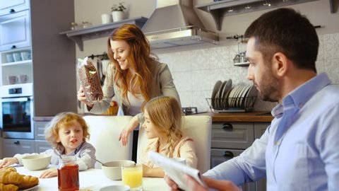 Caucasian little boy, girl and father siting on the table in kitchen. Father reading newspaper, mother filling flakes in plate of son, dauther eating flakes with milk.