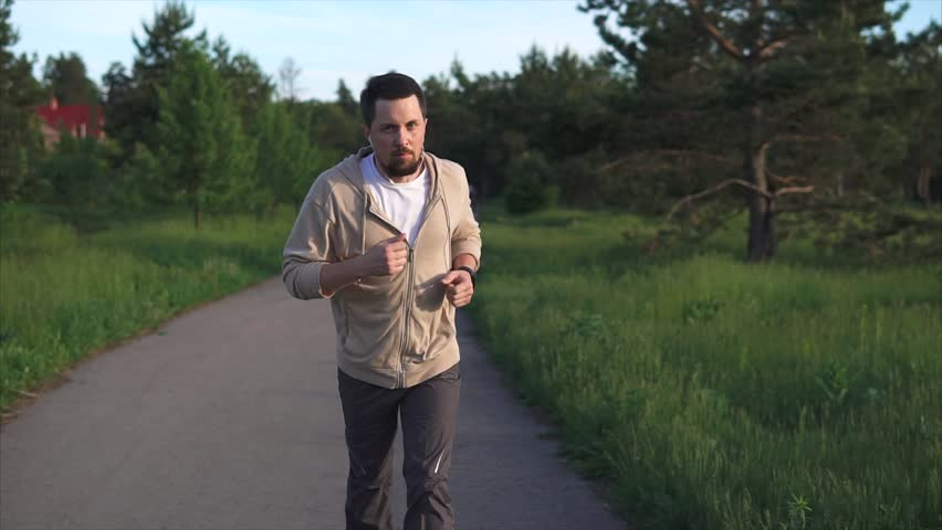 An adult male who listens to music in headphones is engaged in sports running to take part in sprint competitions, the person is in the park #28478920