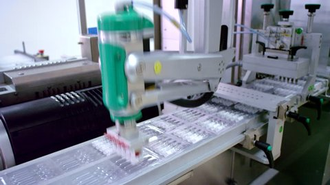 Pharmaceutical manufacturing line. Automated production line. Medicine industry.  Packaging machine. Medical ampoules on conveyor line at drug factory
